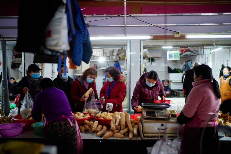 Chineses usam máscara para se prevenir do coronavírus em mercado de Wuhan, na província de Hubei