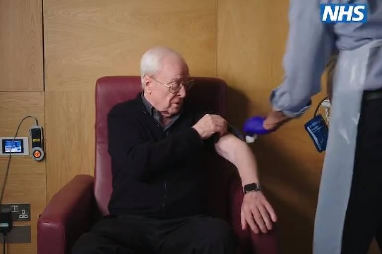 Sentado em uma poltrona marrom, o ator, de preto, levanta a manga da blusa e recebe uma injeção de uma pessoa que está de costas