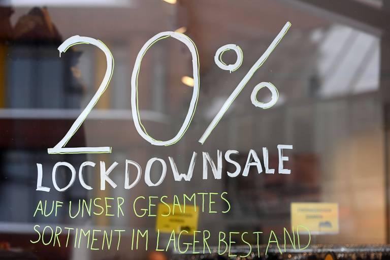 """em branco, um grande 20% está desenhado em uma vitrine, com a frase """"liquidação de confinamento"""" embaixo, em alemão"""
