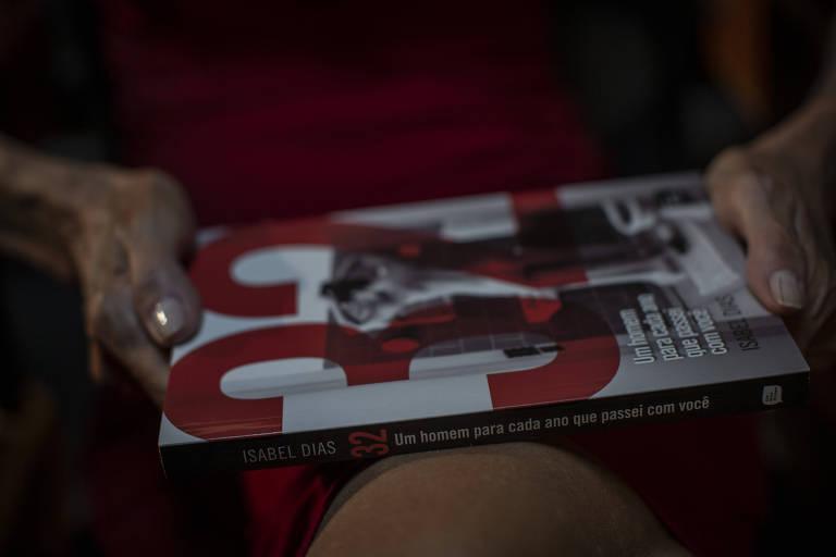 Durante entrevista à Folha, Isabel Dias segura seu livro '32: Um Homem Para Cada Ano Que Passei com Você'