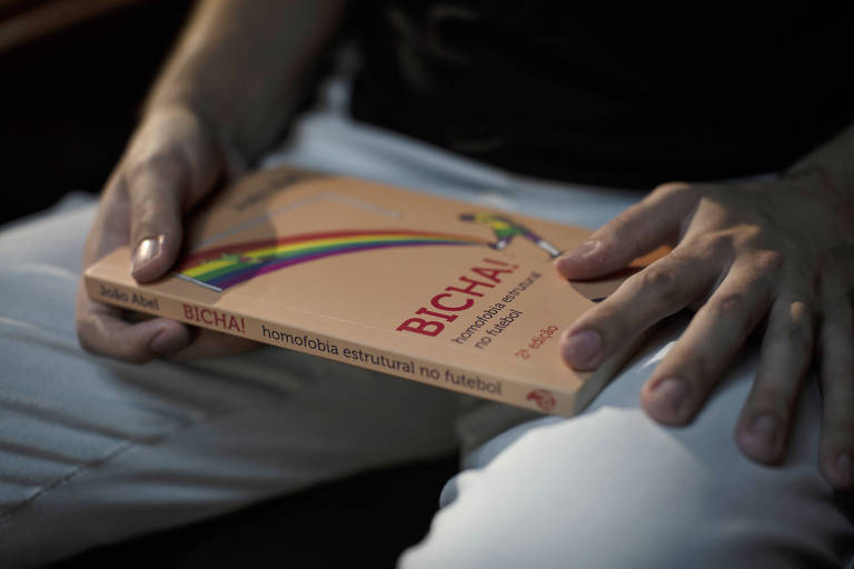 João Abel mostra seu livro 'Bicha!: A Homofobia Estrutural no Futebol', durante entrevista à Folha