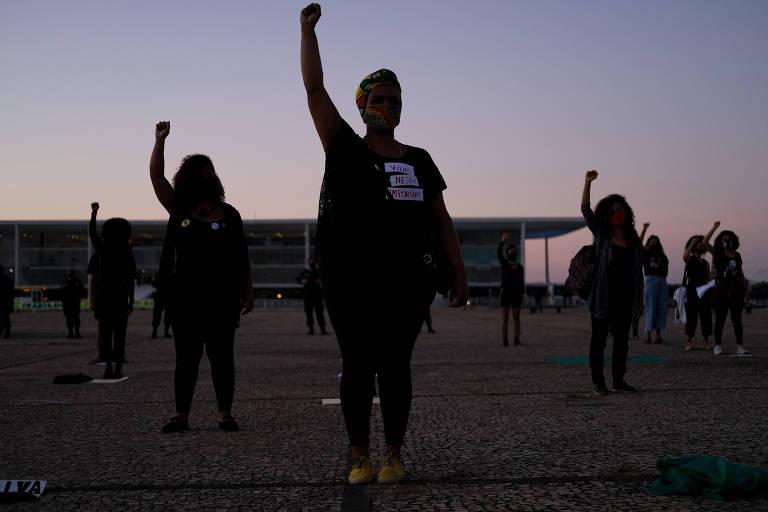 Pessoas em pé com a mão direita erguida como símbolo de resistência na Praça dos Três Poderes