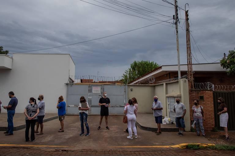 Pessoas mantêm distância em fila em uma calçada