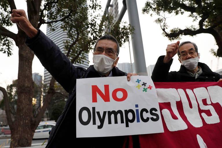 Pessoas erguem cartazes rejeitando realização dos jogos
