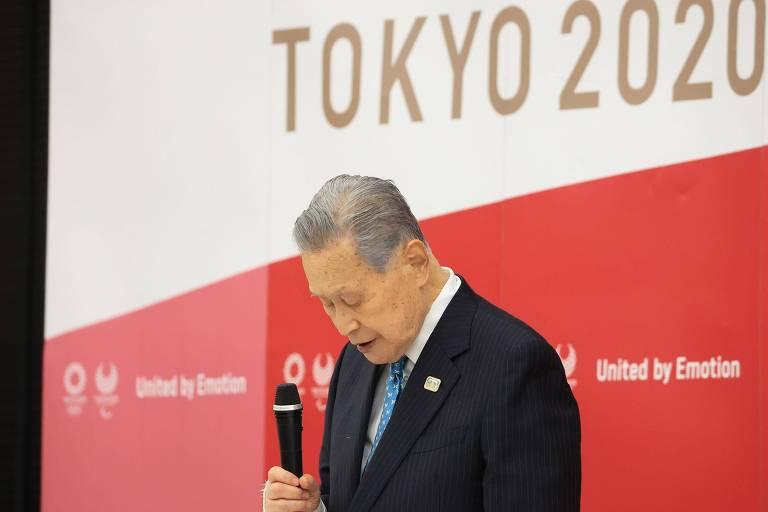Yoshiro Mori abaixa a cabeça com o microfone na mão à frente de um painel de Tóquio-2020