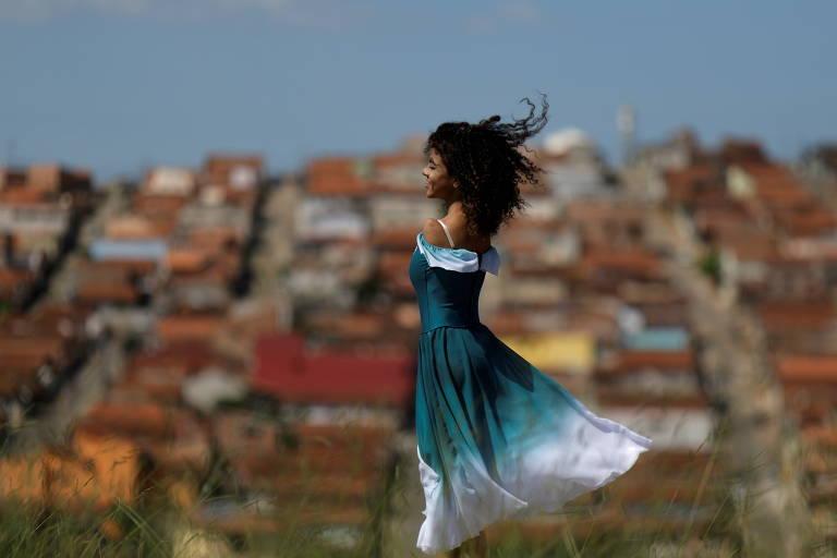 Bailarina sem braço posa para foto em frente à bairro de classe média.