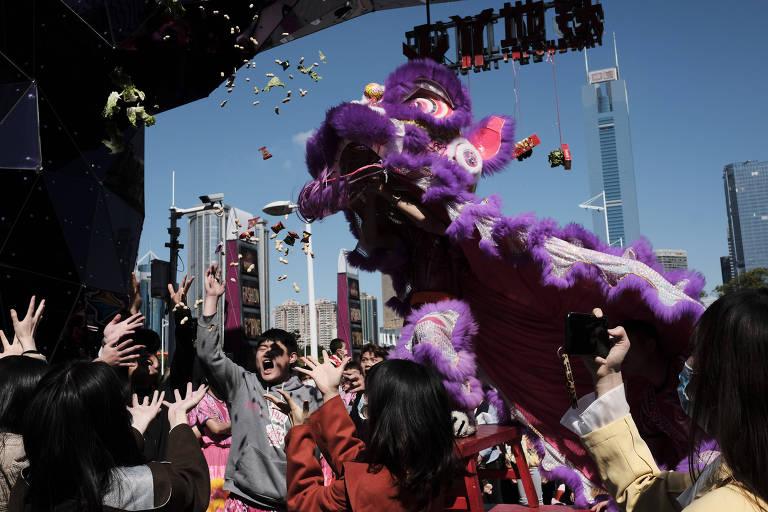 Um homem vestido de dragão joga doces e amendoins para as pessoas na rua.