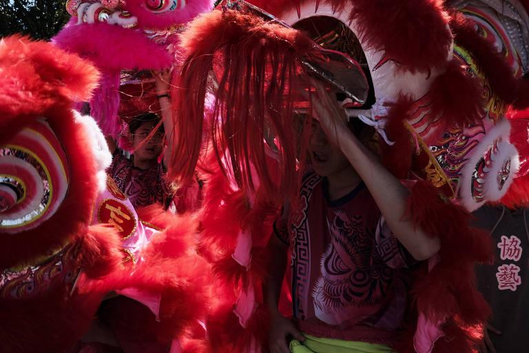 Homens vestem fantasia de dragão durante festa de Ano-Novo em Cantão, na China