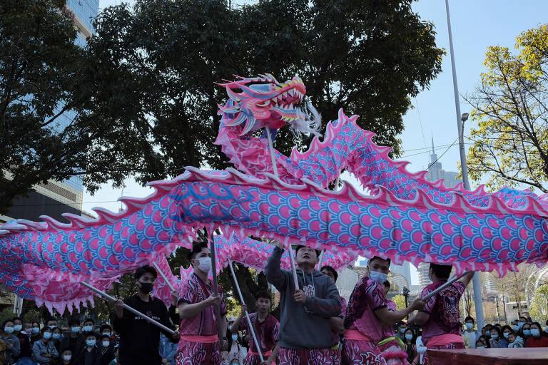 Um grupo se apresenta carregando um dragão.