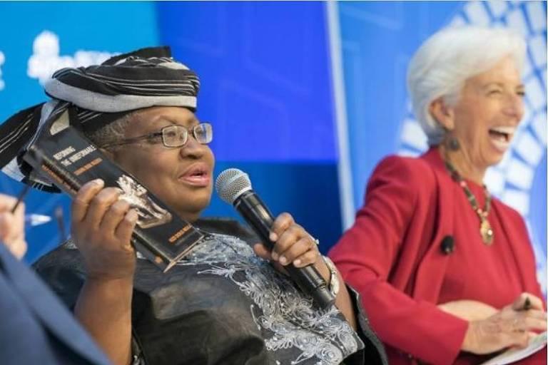 À direita, mulher grisalha de roupa vermelha dá uma gargalhada; à esquerda, mulher de roupas africanas e óculos segura um livro não mão direita e um microfone na mão esquerda