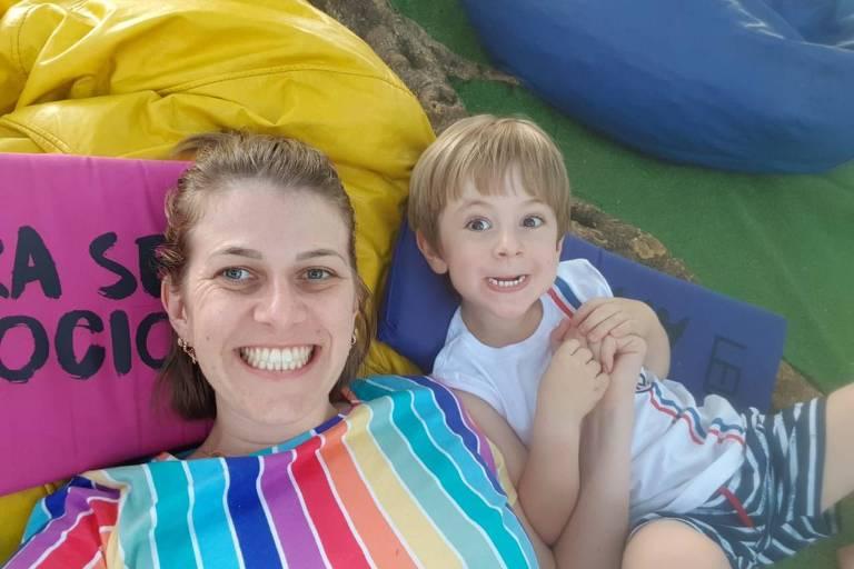 Uma mulher loira com camiseta de arco-íris sorri para a câmera ao lado de um menino loiro de cabelos lisos que faz careta, mostrando os dentes de baixo