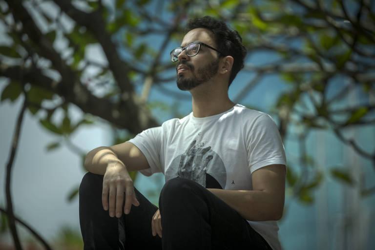 Homem sentado, olhando para a frente, com árvore ao fundo