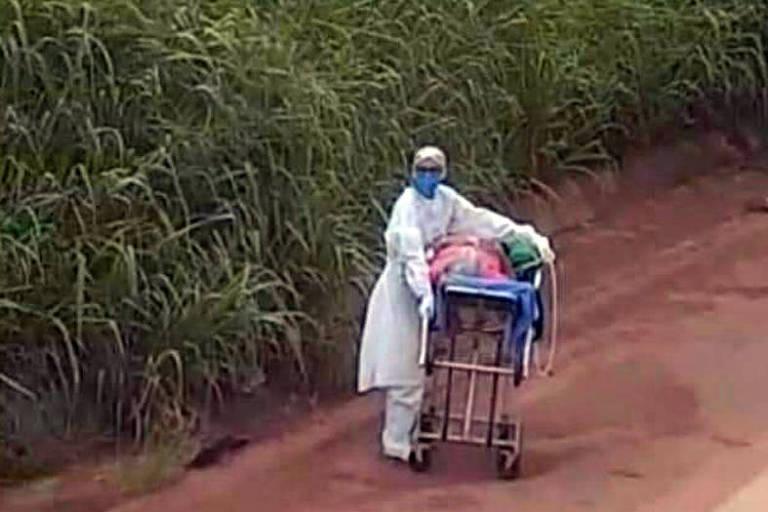 Uma enfermeira com roupas brancas empurra maca em estrada de terra