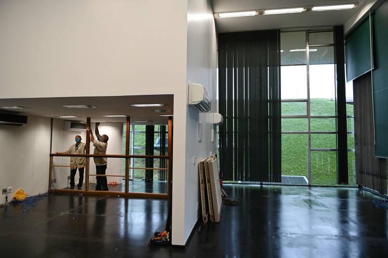Sala vazia. Ao fundo, homens retiram vidro de painéis de madeira.