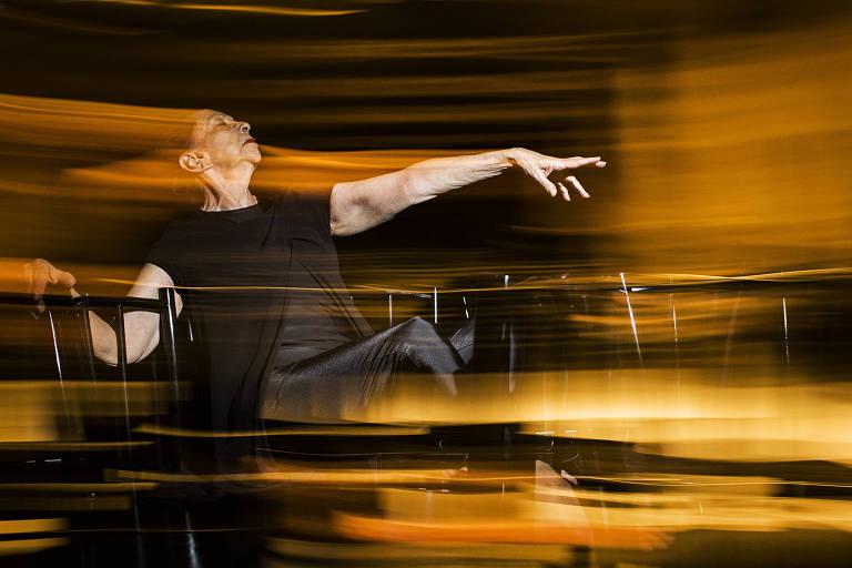 A bailarina Marilena Ansaldi faz uma coreografia sentada numa cadeira, com o braço estendido