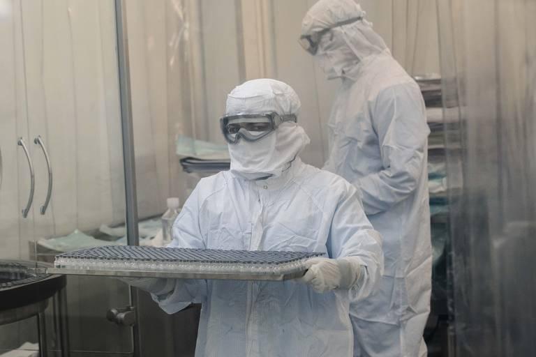 Imagem mostra dois funcionários vestidos com macacãoe capuz brancos e óculos de proteção, um dos quais carregra bandeja, em laboratório