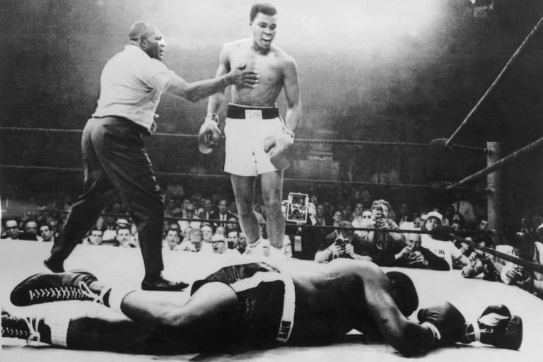 Foto em preto e branco de homem, de calção, em ringue, olhando para outro homem que está caído no chão