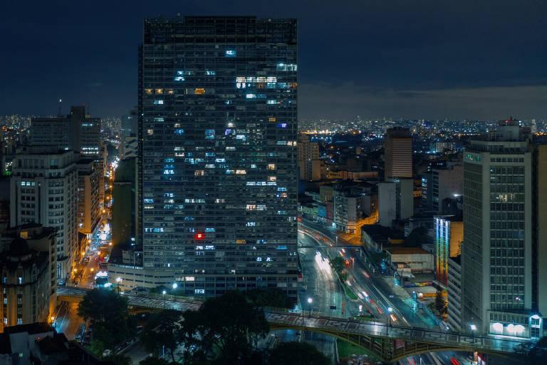 vista de prédios. no centro se destaca um prédio mais alto que todos e retangular