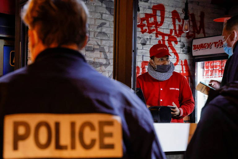 De costas, policial olha para atendente de lanchonete, de roupa vermelha