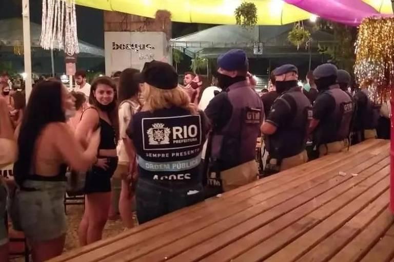 Imagem mostra policiais interditando a festa, com muitas pessoas reunidas e sem usar a máscara corretamente