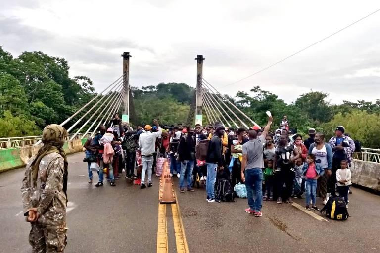 Impedidos de cruzar a fronteira no Brasil para o Peru, imigrantes no lado brasileiro impedem a passagem na ponte da Integração, em Assis Brasil
