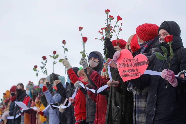 Fileira de mulheres segurando faixa branca e flores