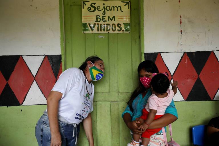 Mulher indígena com criança aguarda para tomar Coronavac no distrito sanitário indígena de Manaus, na Aldeia Correnteza, às margens do Rio Urubu