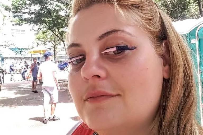 Selfie de mulher loira maquiada usando cílios postiços cor de rosa e blusa vermelha em uma praça