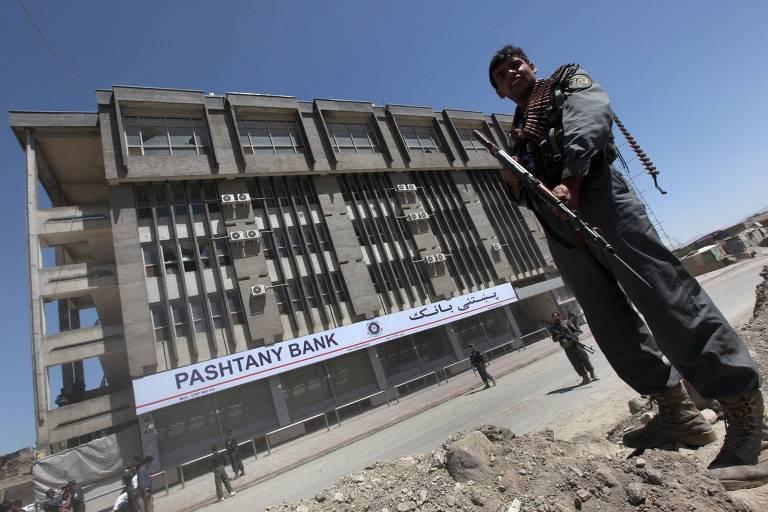 Policial afegão monta guarda em frente a prédio de banco paquistanês, alvo de ataques, em Cabul, Afeganistão