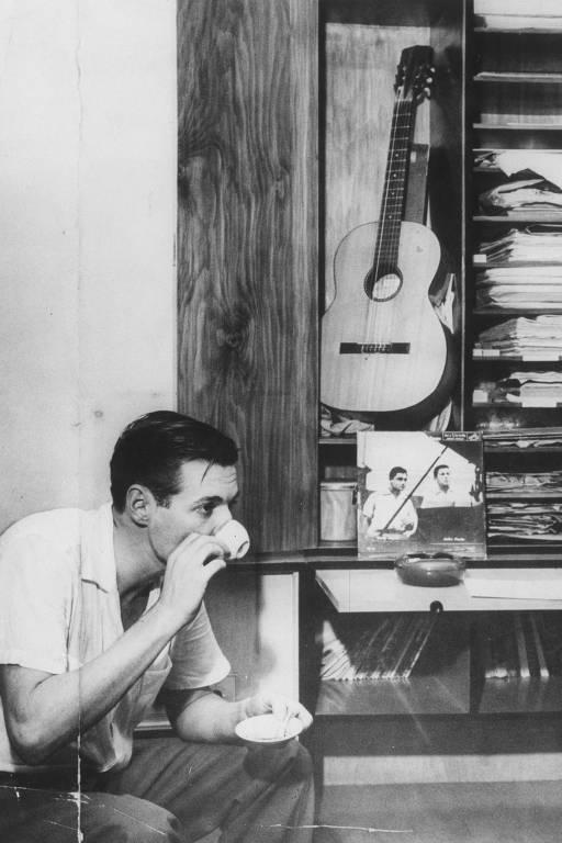 homem de lado tomando café em xicara e segurando o pires com a outra mão. ao fundo, uma estante na qual está um violão
