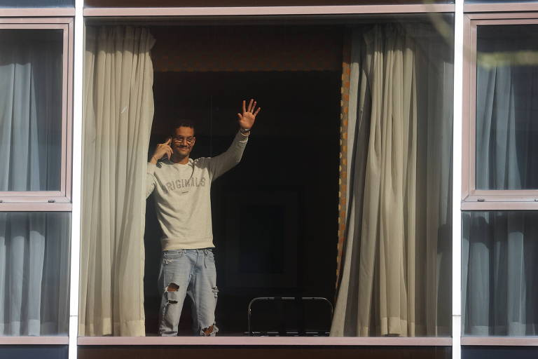 Moço de jeans e camiseta de manga longa acena através de janela
