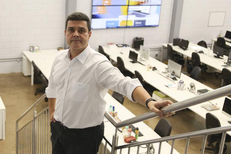 Homem se apoia em corrimão em sala com computadores