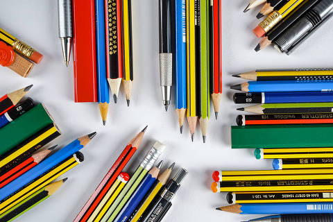 Material escolar enfileirado, incluindo lápis grafite e lápis de cor