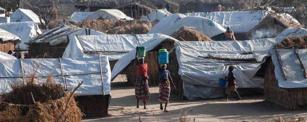 Mulheres levam balde na cabeça em campo de Metuge para deslocados devido ao conflito em Cabo Delgado, no norte de Moçambique