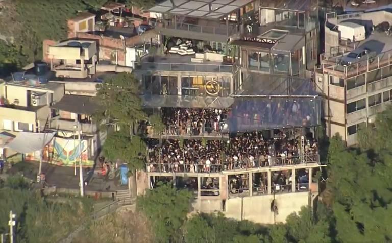 Imagem aérea mostra uma boate de ao menos três andares lotada de pessoas no Morro do Vidigal