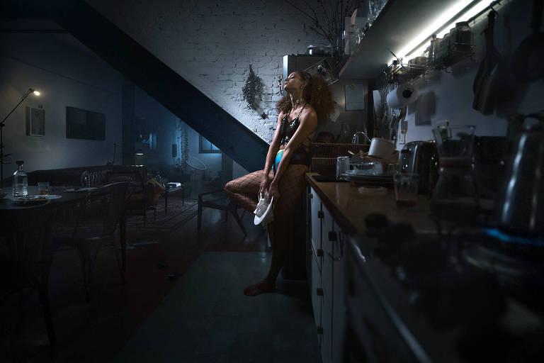 Mulher fantasiada para o carnaval posa em sua cozinha enquanto seca louça com pano de prato.