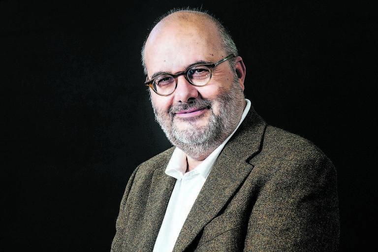 homem branco careca de óculos veste terno marrom e sorri para foto