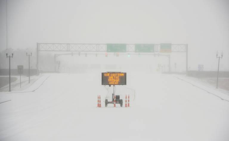 Sinal luminoso no meio de estrada coberta por neve