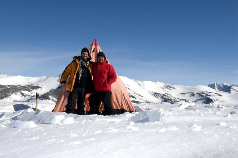 Dois homens com roupas de frio em frente a barraca no meio da neve e gelo