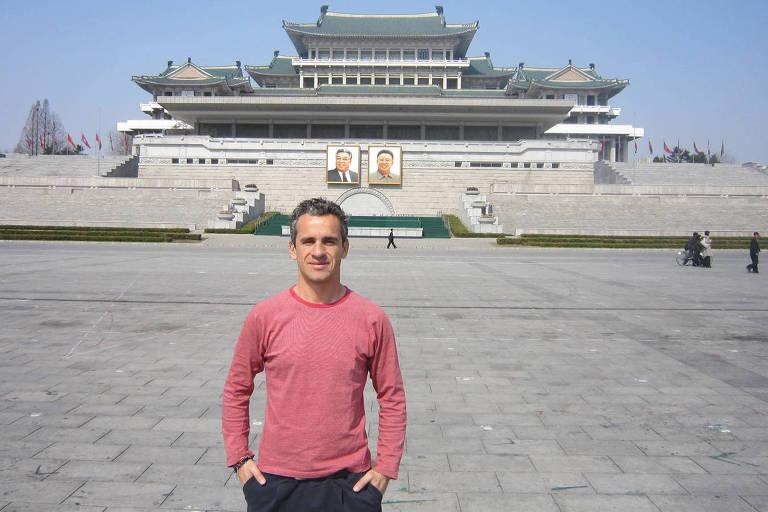 homem vestindo camiseta de manga comprida vermelha diante de enorme palácio em estilo extremo oriente na parede do qual estão dois retratos de homens