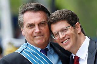 Brazil's President Jair Bolsonaro hugs Brazil's Environment Minister Ricardo Salles during a ceremony of Aviator's Day