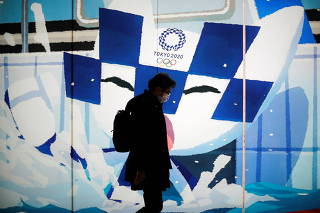 Man wearing a protective face mask walks past in front of an advertising showing Tokyo 2020 Olympic Games mascot Miraitowa, in Tokyo