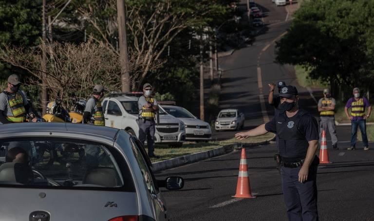 Guardas municipais estão ao lado de cones nas ruas; veículos estão sendo parados em fiscalização