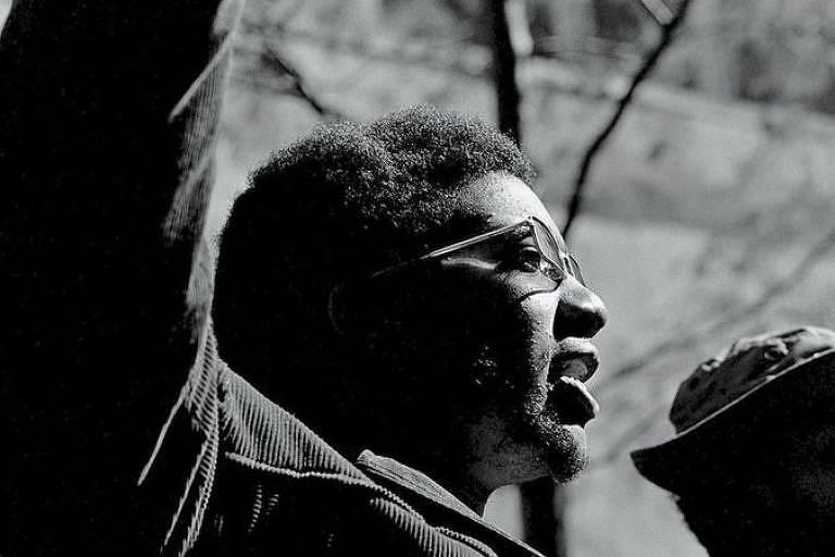 Homem negro com óculos estende braço enquanto discursa