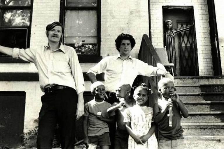 Dois homens brancos ao lado de três crianças negras