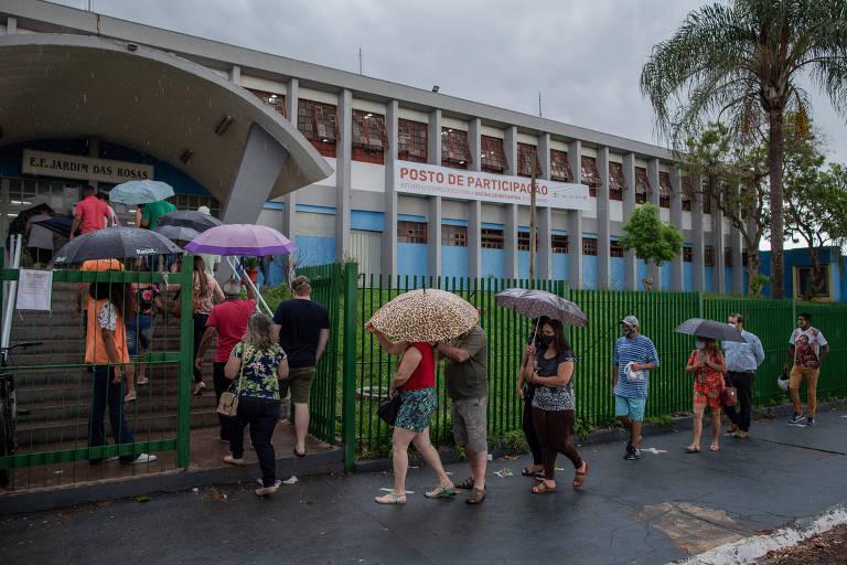 Sob chuva, pessoas usam sombrinhas e guarda-chuvas em fila à espera da vacinação em prédio de Serrana
