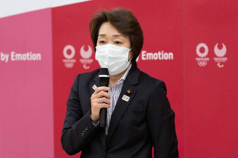 Mulher usando máscara fala ao microfone