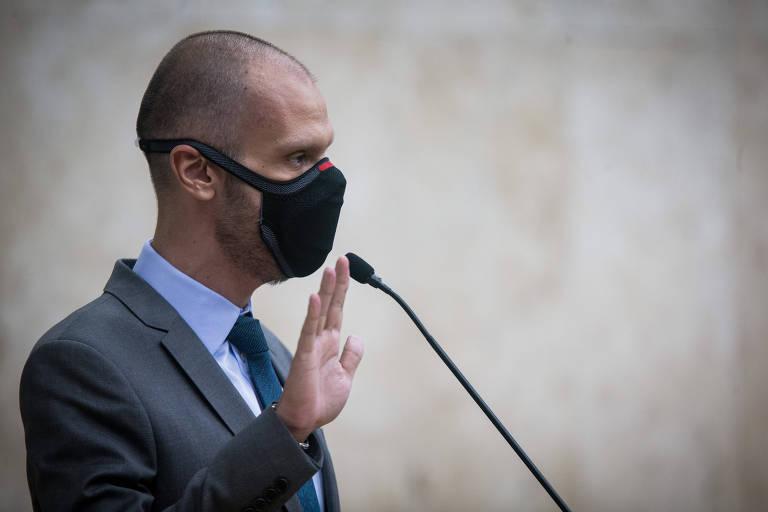 Covas, homem calvo e magro, ergue a mão direita, diante de um microfone, para prestar juramento. Ele usa terno cinza, camisa azul, gravata e máscara de proteção facial