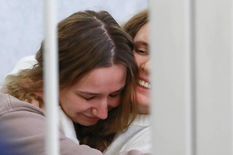 Duas moças se abraçam atrás de grades
