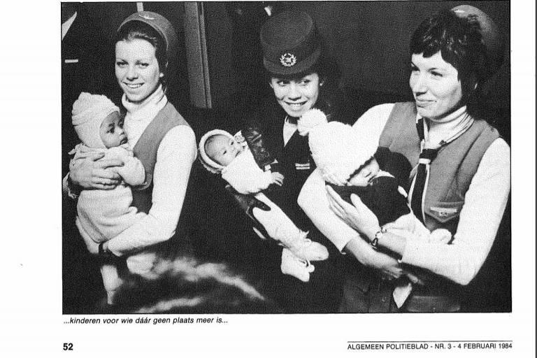Foto em preto e branco com três aeromoças uniformizadas cada uma com um bebê no colo